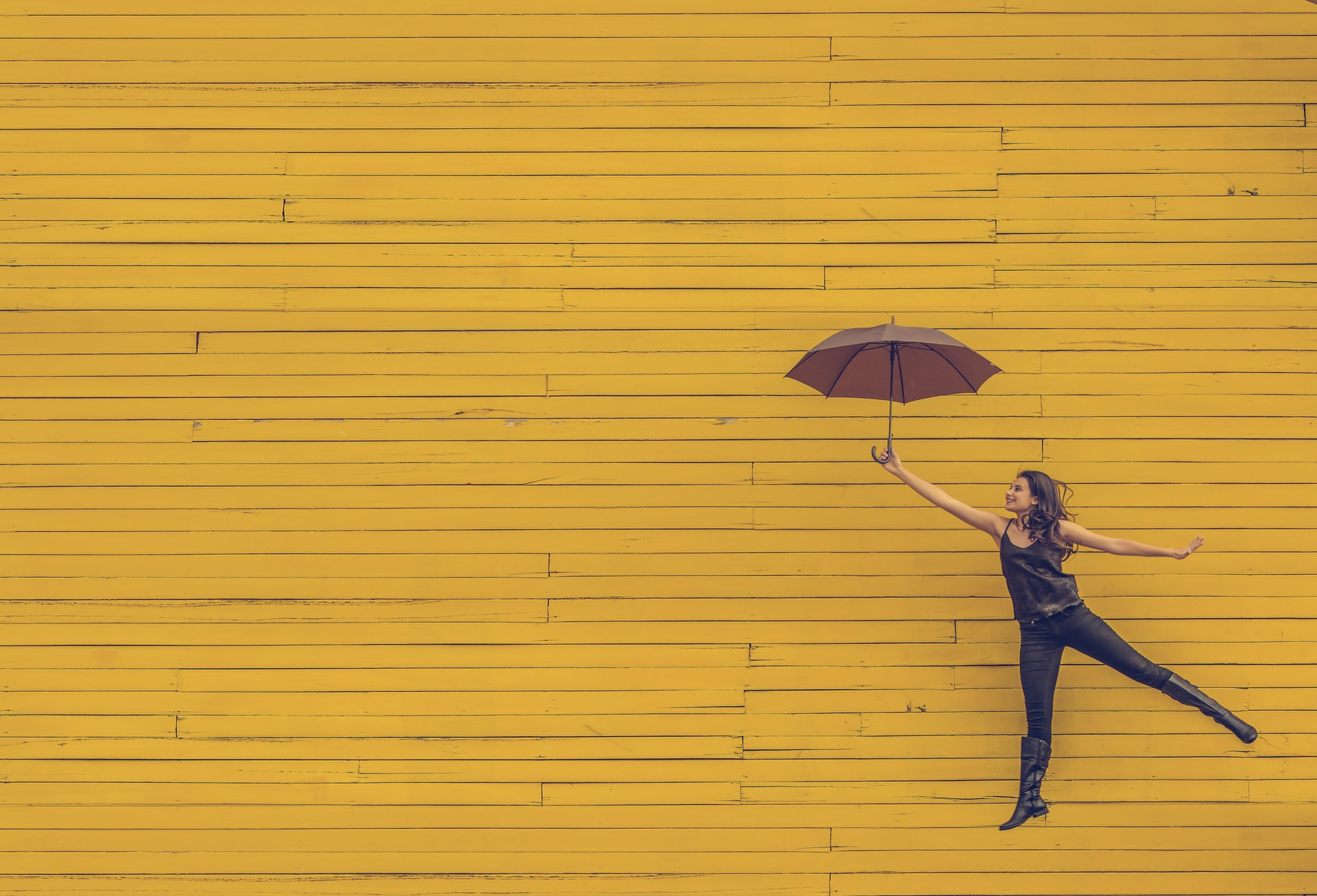 woman leaping against yellow background